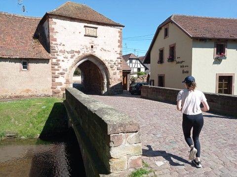 Foulées du patrimoine de Dachstein - une coureuse devant la porte de Dachstein
